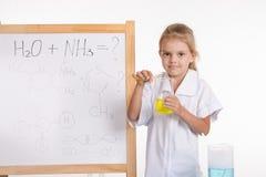 Experiencia química de las demostraciones de la muchacha que se coloca en la pizarra Imagenes de archivo