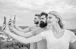 Experiencing digital picture sharing. Best friends taking selfie with camera phone. People shooting selfie on nature royalty free stock photography