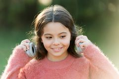 Experiencing excellent sound with new technology. Happy child enjoy listening to music on the go. Adorable little girl. Outdoor. Little girl child wearing royalty free stock photo