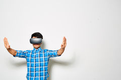 Experiencing Virtual Reality. Confident young man experiencing virtual reality through VR headset while standing against white background Stock Photography