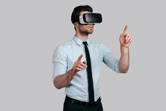 Experiencing virtual reality. Handsome young man in formalwear wearing virtual reality headset and gesturing while standing against grey background Stock Photography