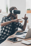 Experiencing virtual reality. Handsome young man with long hair wearing virtual reality headset and gesturing while sitting at his desk in creative office Stock Images