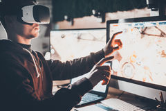 Experiencing virtual reality. Handsome young man wearing virtual reality headset and gesturing while sitting at his desk in creative office Stock Images