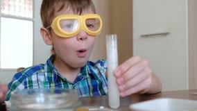 Experimente auf Chemie zu Hause Überraschtes Junge ` s Gesicht, das chemische Reaktion mit der Freisetzung von Gas im Test betrac stock footage