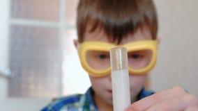 Experimente auf Chemie zu Hause Chemische Reaktion mit der Freisetzung von Gas im Reagenzglas im Jungen, s-Hände stock video