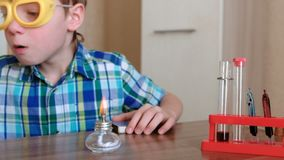 Experimente auf Chemie zu Hause Junge erhitzt das Reagenzglas mit roter Flüssigkeit auf brennender Alkohollampe stock footage