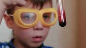 Experimente auf Chemie zu Hause Nahaufnahmejunge ` s Gesicht überprüft den Inhalt des Reagenzglases stock video footage