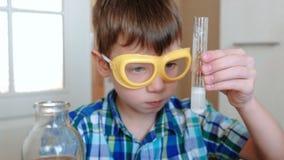 Experimenten op chemie thuis Chemische reactie met de versie van gas in een reageerbuis in de handen van verrast stock footage