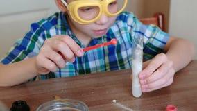 Experimenten op chemie thuis Chemische reactie met de versie van gas in de reageerbuis in de jongen, s-handen stock footage