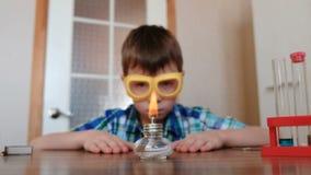 Experimenten op chemie thuis De jongen bekijkt de brandende alcohollamp stock videobeelden