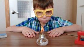 Experimenten op chemie thuis De jongen bekijkt de brandende alcohollamp stock video