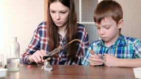 Experimenten op chemie thuis De jongen en zijn mamma verwarmen de reageerbuis met blauwe vloeistof bij het branden van alcohollam stock footage
