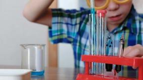 Experimenten op chemie thuis De jongen giet blauwe vloeistof van de beker in de reageerbuis met een pipet stock footage