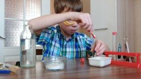 Experimenten op chemie thuis De jongen giet het poeder in het flesje met een spatel stock video