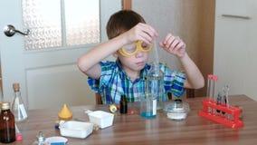 Experimenten op chemie thuis De jongen giet het water in de beker met een andere blauwe substanties stock videobeelden