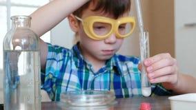 Experimenten op chemie thuis De jongen giet het water in reageerbuis met poeder gebruikend pipet stock footage