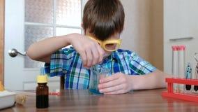 Experimenten op chemie thuis De jongen mengt de blauwe vloeistof en het poeder in de beker met glasstok stock videobeelden