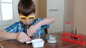 Experimenten op chemie thuis De jongen mengt de substanties en de blauwe vloeistof in de beker stock videobeelden