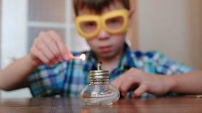 Experimenten op chemie thuis De jongen plaatst de brandende alcohollamp op brand met een gelijke stock videobeelden