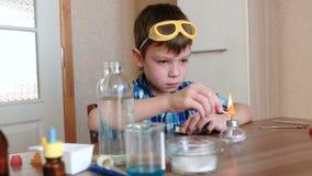 Experimenten op chemie thuis De jongen plaatst de brandende alcohollamp op brand met een gelijke stock footage