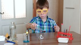Experimenten op chemie thuis De jongen verwarmt de reageerbuis met rode vloeistof bij het branden van alcohollamp stock footage
