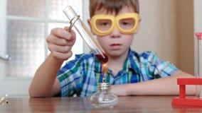 Experimenten op chemie thuis De jongen verwarmt de reageerbuis met rode vloeistof bij het branden van alcohollamp De vloeistof ko stock video