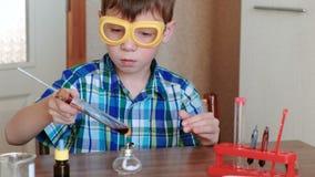 Experimenten op chemie thuis De jongen verwarmt de reageerbuis met rode vloeistof bij het branden van alcohollamp De vloeistof ko stock footage