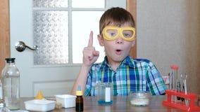 Experimenten op chemie thuis Inzicht of idee van een jonge wetenschapper Boy in plaidoverhemd en beschermende brillen stock video