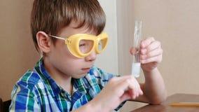 Experimenten op chemie thuis Jongensslagen op een reageerbuis met reagentia die glasstok gebruiken stock video