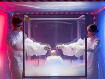 Experimenting on raw meat in sterile chamber. Two scientists, a men and a woman, conducting chemical experiments with liquid nitrogen on a raw chicken in a Royalty Free Stock Images