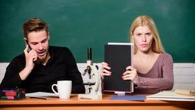 Experimento cient?fico Individuo y muchacha en el escritorio con el microscopio Lecci?n de la biolog?a Estudiantes que estudian l imágenes de archivo libres de regalías