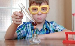 Experiments on chemistry at home. Boy heats the test tube with red liquid on burning alcohol lamp. Royalty Free Stock Image