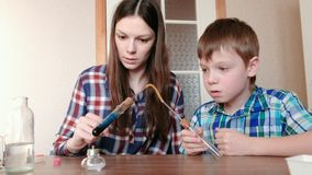 Experiments on chemistry at home. Boy and his mom heat the test tube with blue liquid on burning alcohol lamp. The. Liquid boils stock video footage