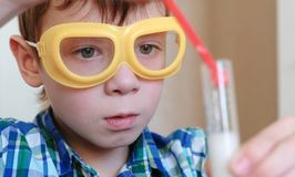 Experiments on chemistry at home. Boy look at Chemical reaction with the release of gas in the test tube in the boy,s. Experiments on chemistry at home. Chemical stock images