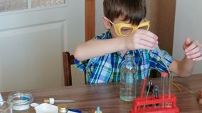 Experiments on chemistry at home. Boy takes a bottle of water and pours water into the tube with a pipette. Side view. Experiments on chemistry at home. Boy stock video footage