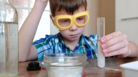 Experiments on chemistry at home.Chemical reaction with the release of gas in the test tube in the boy,s hands. Experiments on chemistry at home.Chemical stock video