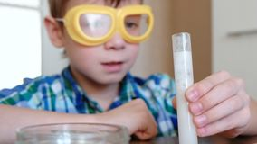 Experiments on chemistry at home.Chemical reaction with the release of gas in the test tube in the boy,s hands. Experiments on chemistry at home.Chemical stock footage