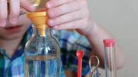 Experiments on chemistry at home. Closeup boy`s hand pours water from bottle into the tube with a pipette. Front view. Experiments on chemistry at home. Closeup stock footage
