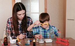 Experiments on chemistry at home. Mother and son do a science experiment together. Experiments on chemistry at home. Mother and son do a science experiment royalty free stock images