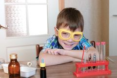 Experiments on chemistry at home. Smiling boy in checkered shirt sits at the table and going to practice chemistry. Experiments on chemistry at home. Boy in stock image