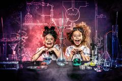 Experiments in laboratory. Funny school children doing experiments in the laboratory. Explosion in the laboratory. Science and education stock image