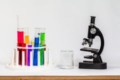 Experiments in mixing chemical substances into glass tube. S with a microscope in a science lab with a white background royalty free stock photo