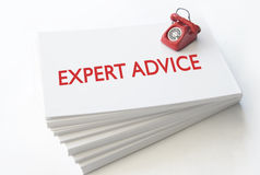 Expert advice. Small telephone on top of a stack of business cards with expert advice stock images