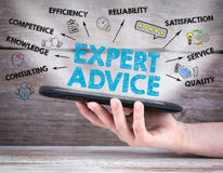 Expert Advice. Tablet computer in the hand. Old wooden background.  Royalty Free Stock Photos