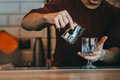 Expert barman is making cocktail. At night club Royalty Free Stock Images