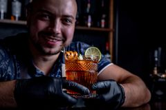 Expert barman is making cocktail at night club. Professional bartender at work in bar pouring sweet drink into glass on. Party at night club. Barman is royalty free stock photos
