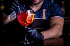 Expert barman is making cocktail at night club. Professional bartender at work in bar pouring sweet drink into glass on. Party at night club. Barman is royalty free stock photo