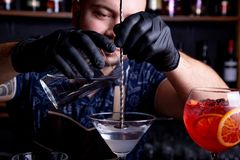 Expert barman is making cocktail at night club. Professional bartender at work in bar pouring sweet drink into glass on. Party at night club. Barman is stock photos