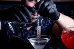 Expert barman is making cocktail at night club. Professional bartender at work in bar pouring sweet drink into glass on. Party at night club. Barman is stock photography