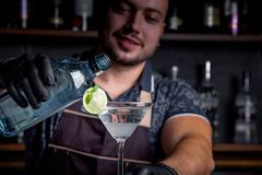 Expert barman is making cocktail at night club. Professional bartender at work in bar pouring sweet drink into glass on. Party at night club. Barman is stock image